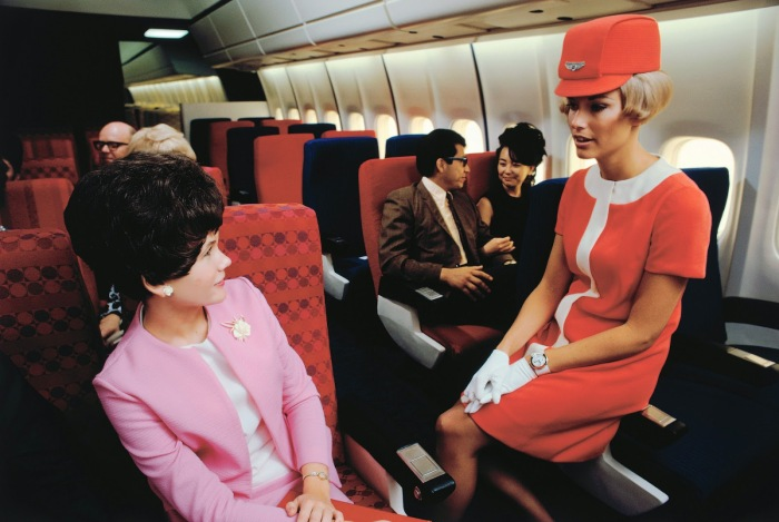 A United Airlines stewardess chats to a passenger in a simulated cabin of a Douglas DC-10, 1968.